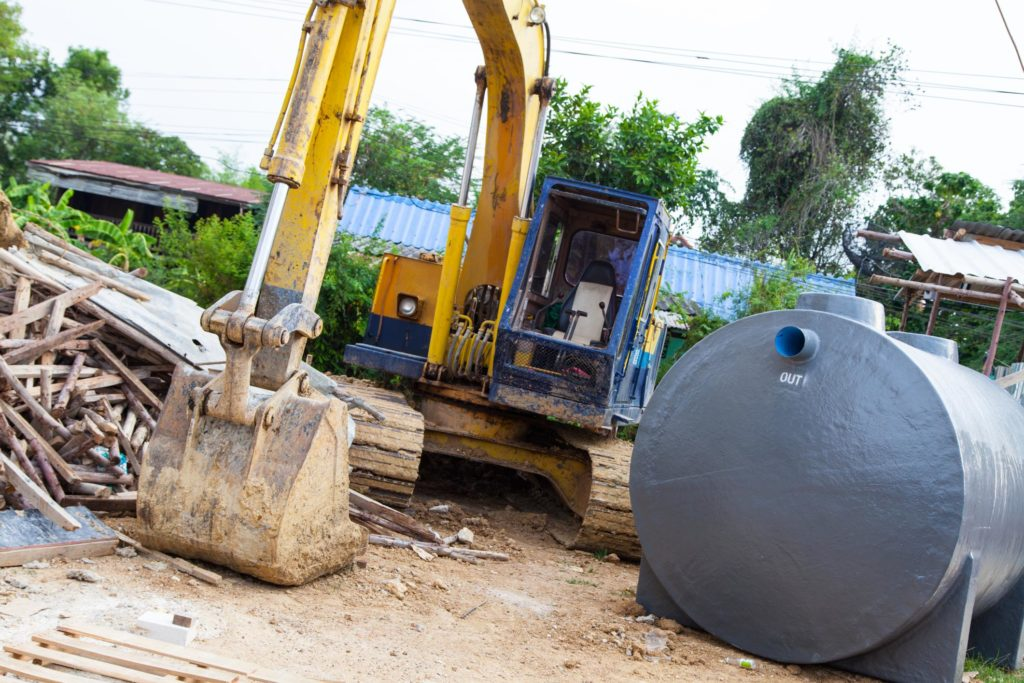 a backhoe truck and septic tank